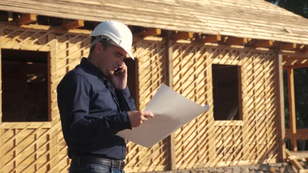 concept building constructing architect slow motion video. man builder in a helmet stands at a construction holding a scheme lifestyle house plan. site near a wooden frame house under construction