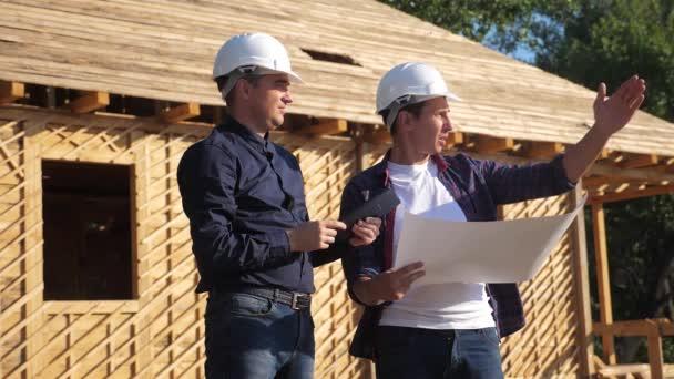 Týmová práce. koncept stavba stavba architekt pomalý pohyb videa. dva muži v helmách studují digitální tabletový plán. dva architekti pracující na stavbě životního stylu rám House