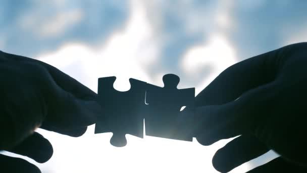 koncepce podnikových financí. mužská ruka spojují dvě skládanky, siluety proti západu slunce. symbol týmové práce přidružení a připojení. strategie podnikání