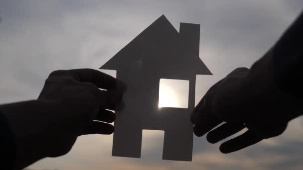 šťastný koncept výstavby rodinných domů. Muž, který drží doma papírový domek ve svém životním stylu a má ruce za slunečních paprsků. životní ekologie symbol videa