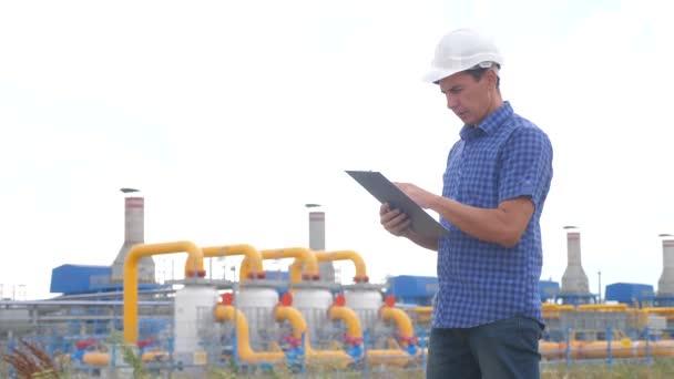 Teamwork Gasproduktionsstationskonzept. Ingenieur Mann stehen schreibt Lifestyle-Dokumente auf dem Tablet weißen Schutzhelm. Mann Ingenieur in Helmarbeit am Bahnhof studieren auf einer Gasversorgung