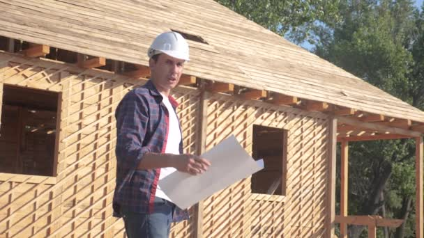 concept building constructing architect slow motion video. man builder in a helmet stands at construction holding a scheme house plan. site near a wooden frame house under construction. lifestyle