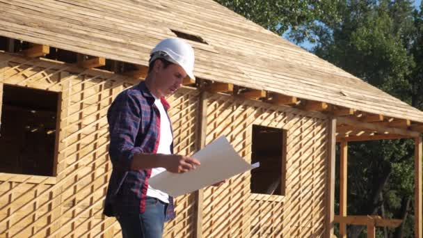concept building constructing architect slow motion video. man builder in a helmet stands at construction holding a scheme house plan. site near a wooden lifestyle frame house under construction