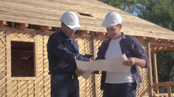 Teamwork. Konzept Gebäude Bau Architekt Zeitlupe Video. Zwei Männer in Helmen studieren den Grundriss des Hauses. Zwei Architekten arbeiten am Bau eines Fachwerkhauses Lifestyle-Business-Kontrast