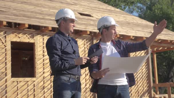 teamwork. concept building constructing architect slow motion video. two men builder in helmets study digital tablet the house plan. two architects working on construction of frame house lifestyle