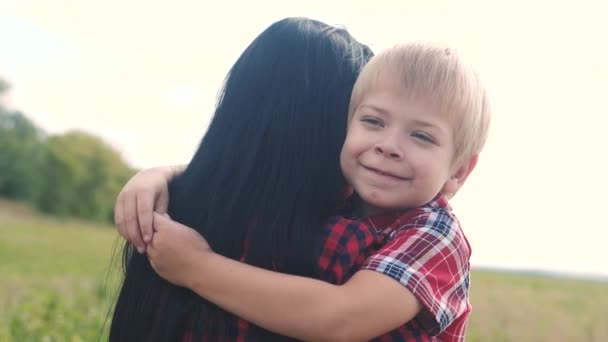 happy family. mom and son happiness love teamwork concept. gentle touching slow motion video. son little boy hugs mom girls outdoors. happy family blond a lifestyle boy and mom brunette