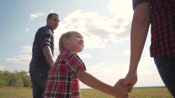 glücklich Familie Wandern Natur Teamwork Freundschaft Pflege Konzept Zeitlupe Video. Vater, Mutter und Sohn gehen in der Natur bei Sonnenuntergang Hand in Hand. glückliche Familieneltern Mann und Mädchen halten kleinen Jungen beim Gehen