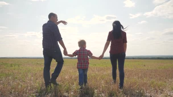 happy family walking nature teamwork friendship care concept slow motion video. father mom and son walk in nature sunset sunlight hold hand. happy family parents man and girl hold little boy a walking
