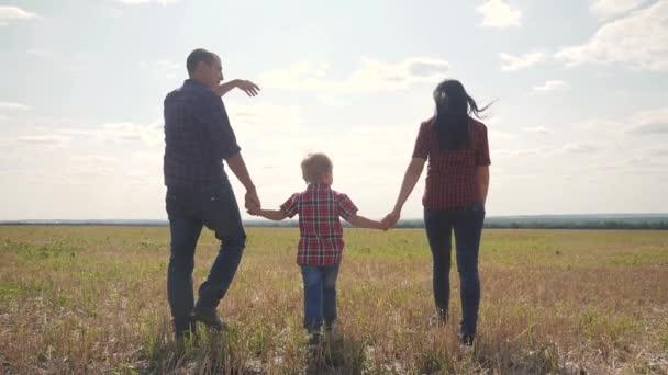šťastná rodina pěší chůze příroda týmova přátelský péče koncept pomalý pohyb video. otec mamka a syn chodí v přírodě slunce na slunci. šťastné rodinné rodiče muž a dívka drží malého chlapce chůze