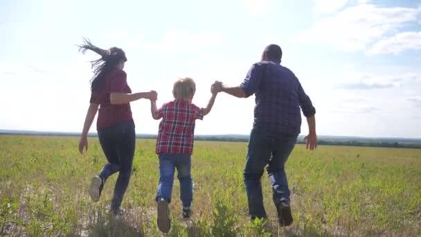 šťastná rodina provozuje přírodu teampráce přátelství péče koncept pomalý pohyb video. otec mamka a syn, kteří běží v přírodě sluneční svit se drží za ruku. šťastné rodinné rodiče muž a dívka držet životní styl malý chlapec