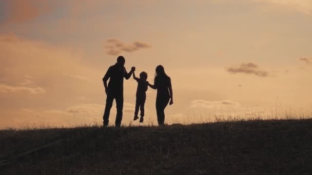 happy family father, mother and son outdoors silhouette concept slow motion video. dad man mom girl hold little boy son by hands. little boy jumping silhouette at sunset outdoors. happy lifestyle
