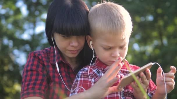 Happy rodina vtipné video zpomalení hrát hudbu týmová práce venku. Máma životní styl a syn poslouchat hudbu na smartphone ve stejných sluchátkách pro dva. šťastná rodina matka žena a syn malý chlapec utrácet