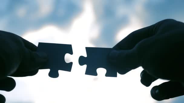 koncepce podnikových financí. mužské ručičky spojují dvě hádanky s siluetou životního stylu západu slunce. symbol týmové práce přidružení a připojení. strategie podnikání