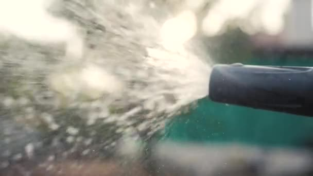 gardening garden care concept. splashing water slow motion video. woman holding a garden hose watering. Gardener with watering hose and water sprayer on the vegetable lifestyle