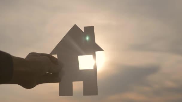 glückliche Familie Bau Haus Konzept. Mann mit einem Lifestylehaus aus Papier in der Hand im Sonnenuntergang. lebensökologisches Videosymbol