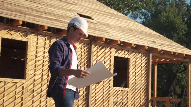 concept building constructing architect slow motion video. man builder in a helmet stands at construction holding a scheme house plan. site near a wooden frame lifestyle house under construction