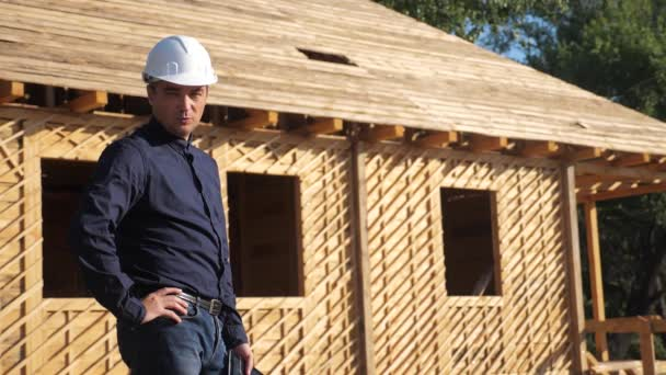 concept building constructing architect slow motion video. man builder in a helmet stands at construction holding digital tablet a scheme house plan. site near a wooden frame house under construction