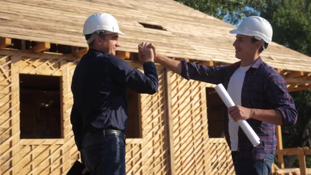 teamwork handshake. concept building constructing architect slow motion video. two men builder in helmets shake hands contract business contrast at a construction site. two workers in helmets