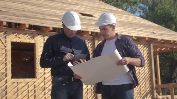 Csapatmunka. koncepcióépítés építész lassított felvételeket készít. Két sisakos férfi tanulmányozza a ház tervét. két építész dolgozik építési keret ház üzleti kontraszt a