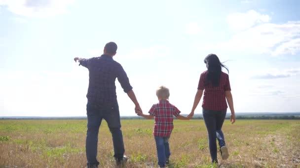 šťastná rodina pěší chůze příroda týmova přátelský péče koncept pomalý pohyb video. životní styl otec matka a syn chodí do přírody sluneční svit na slunci. šťastné rodinné rodiče muž a dívka drží malého chlapce