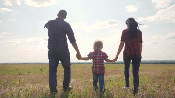 šťastná rodina procházka příroda životní styl týmově přátelství péče koncept pomalý pohyb video. otec mamka a syn chodí v přírodě slunce na slunci. šťastné rodinné rodiče muž a dívka drží malého chlapce