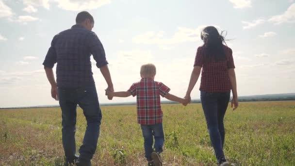 glücklich Familie Wandern Natur Teamwork Freundschaft Pflege Konzept Zeitlupe Video. Vater, Mutter und Sohn gehen in der Natur bei Sonnenuntergang Hand in Hand. glückliche Familie Eltern Mann und Lifestyle Mädchen halten kleinen Jungen