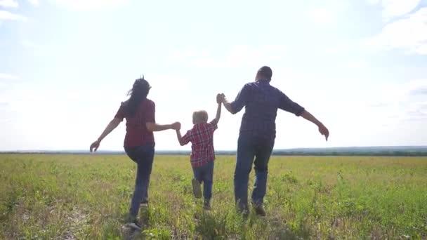 šťastná rodina provozuje přírodu teampráce přátelství péče koncept pomalý pohyb video. otec mamka a syn, kteří běží v přírodě sluneční svit se drží za ruku. šťastný rodinný rodič muž životní styl a dívka držet malého chlapce