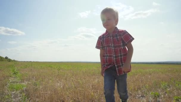 happy family superhero concept little boy runs. boy a schoolboy runs across the field in nature slow motion video. childhood dreams lifestyle of freedom