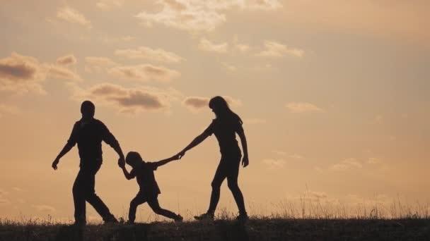 šťastné rodinné týmové práce. chodit s otcem, matkou a synem venku představa pomalého pohybu videa. táta chlap máma má životní styl a chodící chlapeček syn rukama. malý chlapec přeskakující siluetu