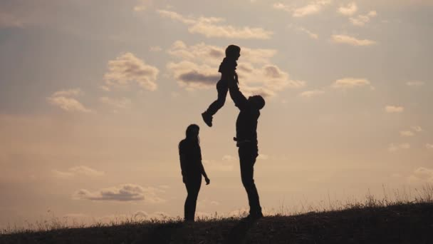 šťastné rodinné týmové práce. Veselý, veselý otec, který se baví, se rozhází ve vzdušném dítěti. otcové den. šťastný rodinný životní styl otec matka a syn silueta slunce při slunci