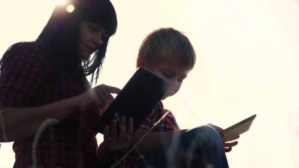 šťastná rodinná koncepce Maminka a syn zpomalují video. Mamka a syn malý chlapec s digitálními tabletky pracuje a hraje na poslední světlici venku. šťastný rodinný digitální životní styl život online