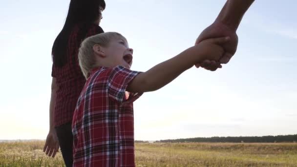 glücklich Familie kleiner Junge ein hält Eltern Hand zu Fuß gehen gehen Zeitlupe Video-Konzept. glückliche Teamarbeit Papa Mann Mutter Mädchen und Sohn Junge Kind halten Hand gehen auf dem Feld in der Natur. Familie mit glücklichem Lebensstil