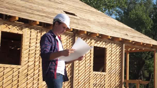 Konzept Gebäude Bau Architekt Zeitlupe Video. Man Builder in Lebensstil ein Helm steht auf der Baustelle mit einem Plan Haus. Grundstück in der Nähe eines im Bau befindlichen Fachwerkhauses
