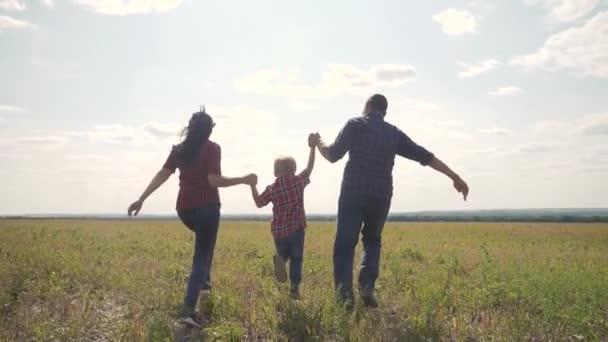 šťastná rodina provozuje přírodu teampráce přátelství péče koncept pomalý pohyb video. otec mamka a syn, kteří běží v přírodě sluneční svit se drží za ruku. šťastné rodinné rodiče muž a životní styl holka drží malého chlapce