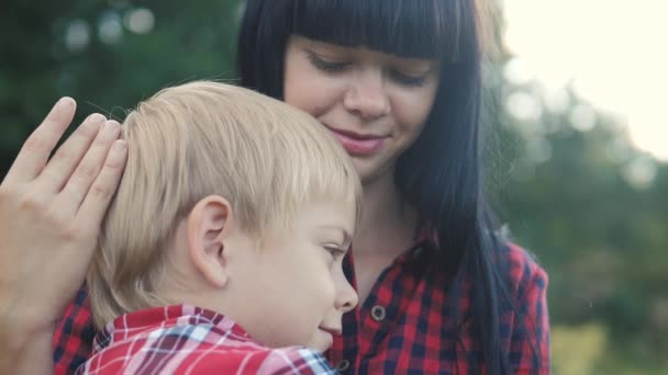 happy family mom and son concept . mom tender childhood video. lifestyle slow motion video. mom a brunette girl protects caress gently hugs takes care of the son boy blonde outdoors
