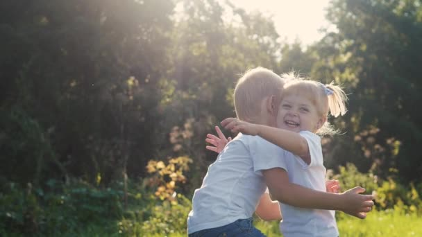 Šťastná rodina: malý chlapec krouží v objetí a dívčí bratr a sestra se drží koncepce šťastných dětí v přírodě. děti se navzájem ohlédly do očí pomalému pohybu video. Dětství