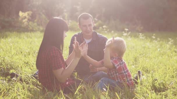 glücklich Familie Teamwork im Freien Konzept im Freien Zeitlupe Video. Mama Papa a und Sohn in Lebensart Natur sitzen auf dem Gras Spaß haben. spielen Mutter Mädchen Papa Mann und Sohn Junge glücklich Familie