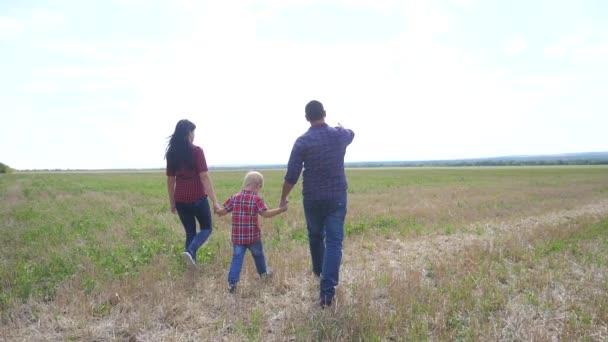 šťastný rodinný tým práce přátelství péče koncept zpomalit video. otec maminka a syn procházka v přírodě západ slunce slunce držet za ruku. šťastný rodina rodiče muž a dívka držet malý životní styl chlapec chůze ruku