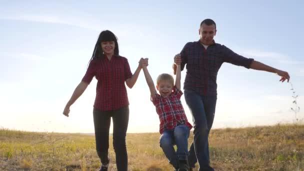 šťastný rodinný otec syn a máma běží zpomalit film zábavné video koncept. šťastný týmová práce táta muž maminka dívka a syn chlapec běh držet ruce běh jít životní styl na poli v přírodě. bezstarostný šťastný