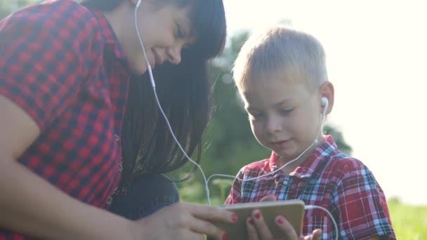 lifestyle šťastný rodina legrační zpomalení video týmová práce venku. Máma a syn poslouchají hudbu na smartphonu ve stejných sluchátkách pro dva. šťastná rodina matka žena a syn malý chlapec trávit čas