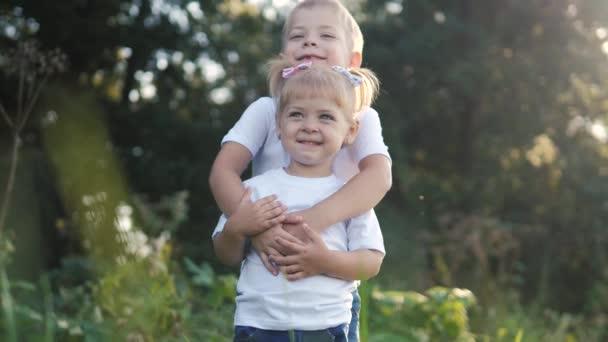 Šťastná rodina: malý chlapec objetí krouží objetí a dívka bratr a sestra držet ruku na přírodě šťastný děti koncept. děti se do sebe dívají očima zpomalené video o životním stylu. děti
