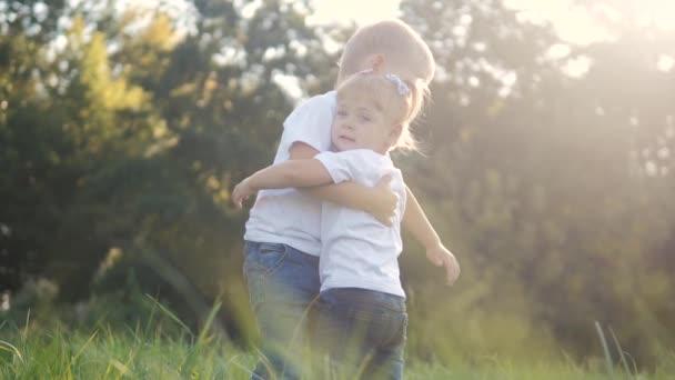Boldog család: a kisfiús ölelések ölelkeznek, és a lány testvér és testvér fogják egymás kezét a természet boldog gyerekek koncepcióján. gyerekek boldog család fiú ölel lány lassított videó. életmód gyerekek