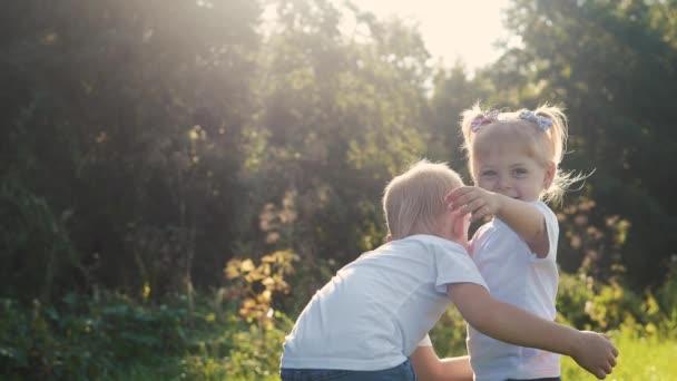 Boldog család: kisfiús ölelések köröznek ölelés egy és lány testvér fogja a kezét a természet boldog gyerekek koncepciója. A gyerekek egymás szemébe néznek lassított felvételen. gyermekkori gyerekek