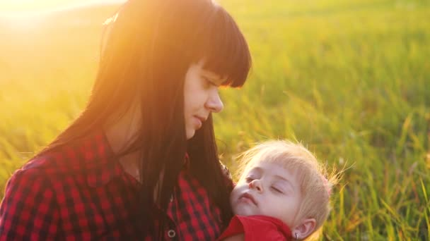 happy family mom holds daughter puts her daughter to bed at sunset slow motion. little girl sleeping in his mother s arms and woman mom play tired falls asleep outdoors sunlight the field outdoors