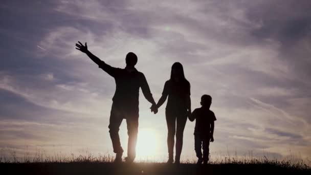 šťastná rodina jít na procházku životní styl týmová práce Silueta, šťastné děti s matkou a otcem, rodina při západu slunce. Máma táta a syn stát chůze na okraji útesu na kopci a sledovat
