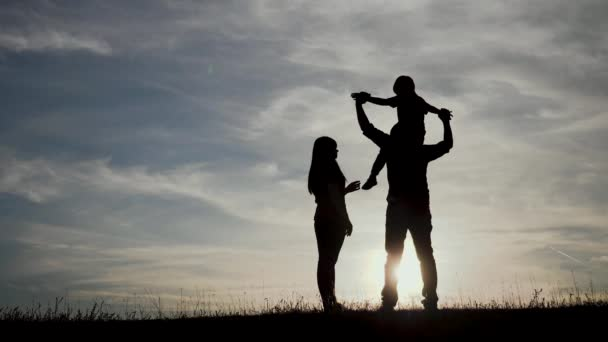 happy family a teamwork Silhouette , happy children with mother and father , family at sunset . mom dad lifestyle and son stand on the edge of cliff of a hill watching a the sunset silhouettes
