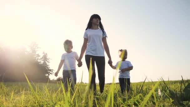 Šťastná rodina legrační chůzi jít za ruce týmová práce Silueta. šťastné děti malý chlapec a dívka s matkou rodiny při západu slunce. maminka a syn maminka dcera životní styl a syn v bílém trička