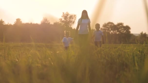 happy family funny walking go for are hold hands a teamwork Silhouette. happy little children boy and girl with mother family at sunset. mom and son mom daughter and lifestyle son in white t-shirts