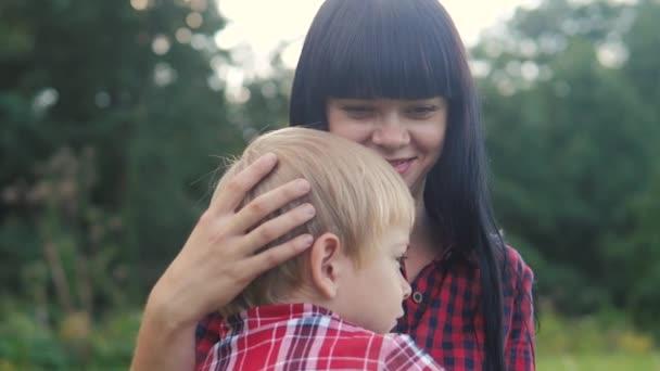 glückliche Familie Mutter und Sohn Konzept. Mama zartes Kindheitsvideo. Zeitlupenvideo. mama lifestyle ein brünettes mädchen sanft umarmt kümmert sich um den sohn junge blond draußen