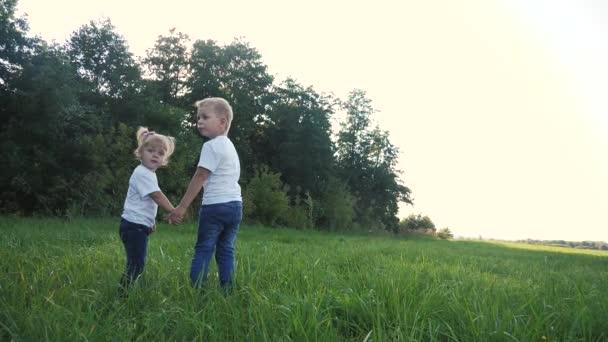 Happy family walking: funny slow motion video malý kluk držet ruce jít příroda hrát vír a dívka bratr a sestra držet ruku na přírodu šťastný děti koncept. děti šťastný rodinný chlapec